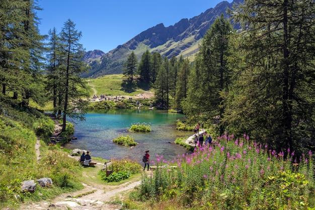 Prachtig shot van een meer in de buurt van de bergen en omgeven door bomen en mensen Gratis Foto