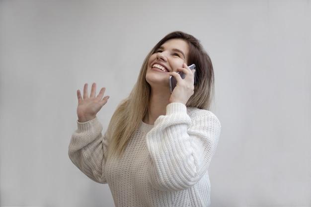 Prachtig shot van een opgewonden vrouw terwijl ze belt vanaf haar telefoon Gratis Foto
