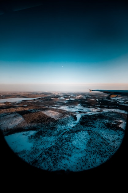 Prachtig shot van een vliegtuigvleugel door het raam over een besneeuwd landschap Gratis Foto
