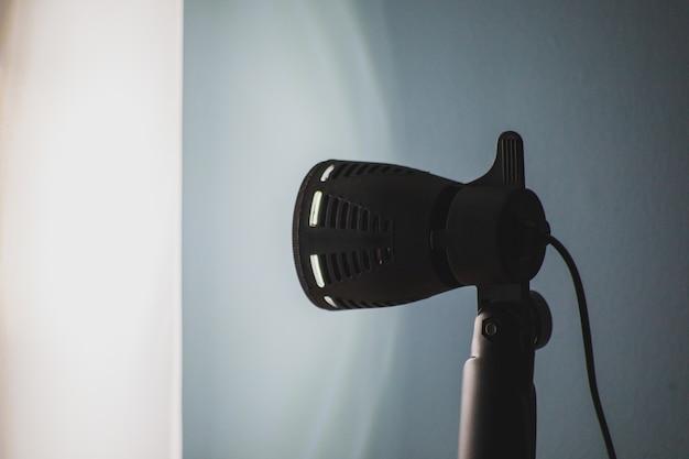 Prachtig shot van een zwart podiumlicht met een blauwe muur Gratis Foto