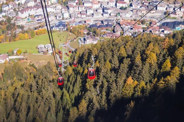 Prachtig shot van kabelbanen boven een beboste berg met gebouwen in de verte Gratis Foto