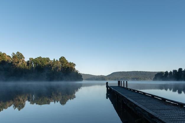 Prachtig shot van lake mapourika in nieuw-zeeland, omgeven door een groen landschap Gratis Foto