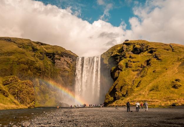 Prachtig shot van mensen die bij de waterval staan met een regenboog aan de zijkant in skogafoss, ijsland Gratis Foto