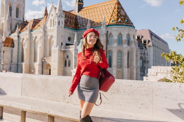 Prachtig slank meisje in trendy kledij staan voor prachtig paleis in zonnige september-dag Gratis Foto