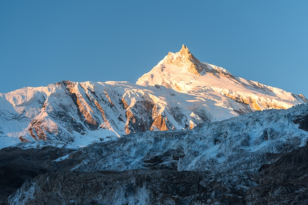 Prachtig uitzicht op besneeuwde berg bij kleurrijke zonsopgang in nepal Premium Foto