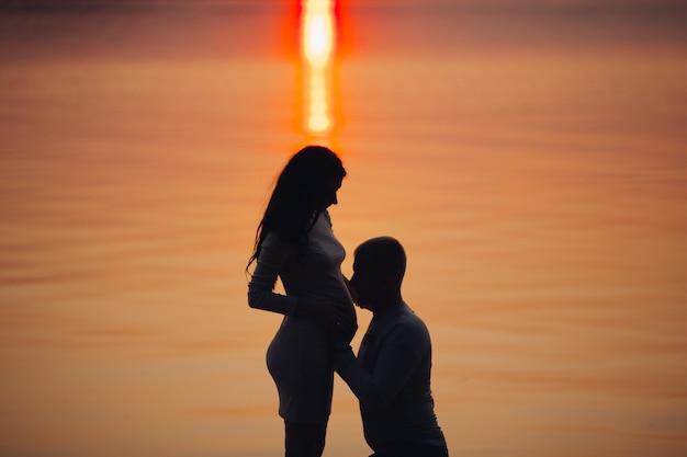Prachtig uitzicht op de man omarmen de buik van zijn vrouw tegen de zee Premium Foto