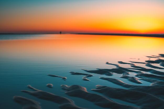 Prachtig uitzicht op de weerspiegeling van de zon in het meer gevangen in vrouwenpolder, nederland Gratis Foto