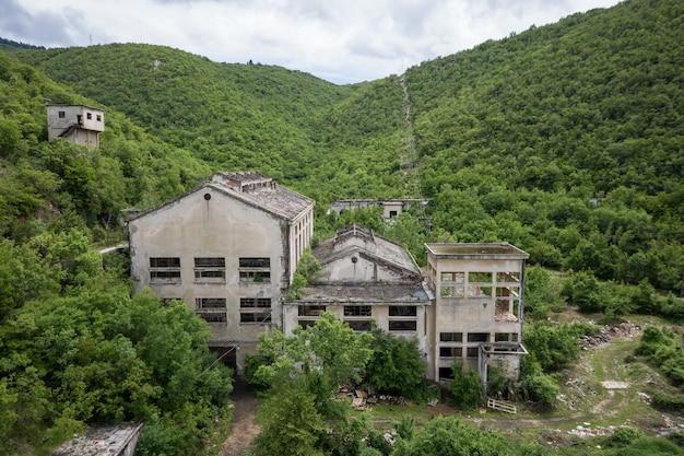 Prachtig uitzicht op een verlaten gebouw omgeven door groene planten Gratis Foto