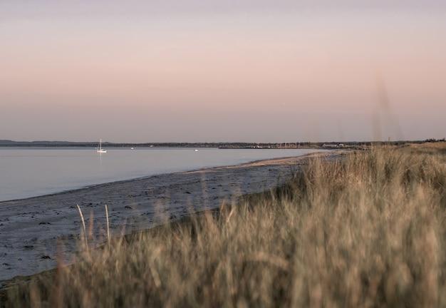 Prachtig uitzicht op strandheuvel op prachtige zonsondergang achtergrond Gratis Foto