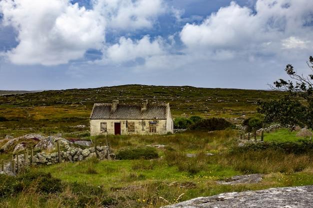 Prachtig uitzicht van een verlaten huisje in county mayo op een grasveld onder de bewolkte hemel Gratis Foto
