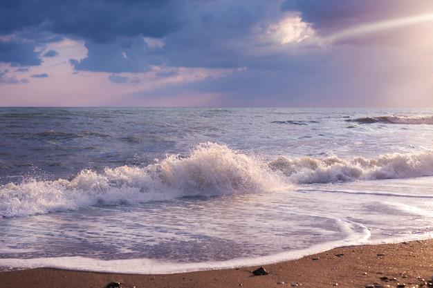 Prachtig zeegezicht met boot op horizon. bewolkte hemel met gouden stralen van de zon, zand kust Premium Foto