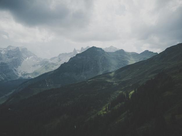 Prachtige berg bedekt met sneeuw onder de mooie mistige hemel Gratis Foto