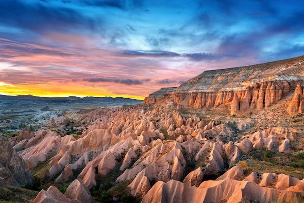Prachtige bergen en rode vallei bij zonsondergang in goreme, cappadocië in turkije. Gratis Foto