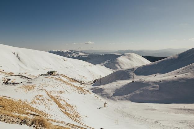 Prachtige besneeuwde winterlandschap panorama met skiresort, blauwe lucht, ski-tracks en skiërs. Premium Foto
