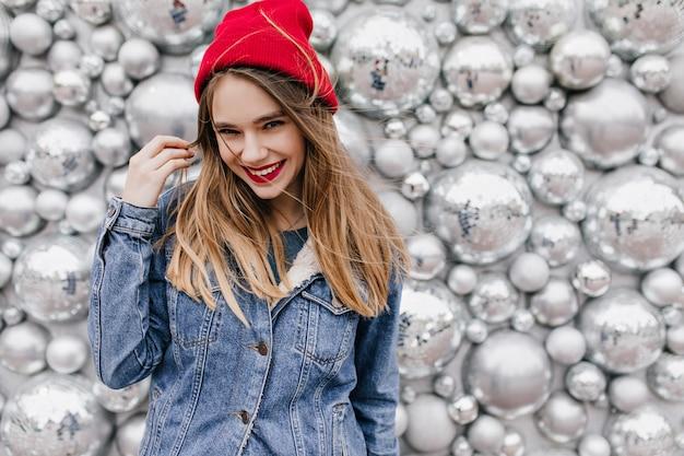 Prachtige blanke vrouw in stijlvol spijkerjasje poseren met lang haar. glimlachend opgewonden meisje in rode hoed die zich voor discoballen bevindt. Gratis Foto