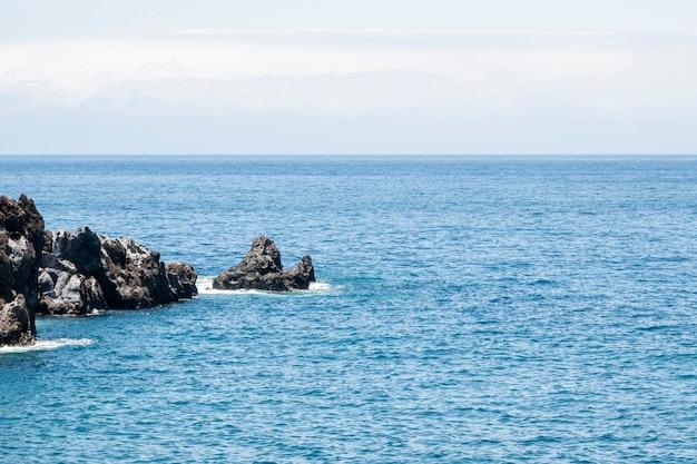 Prachtige blauwe zee met rotsen aan de kust Gratis Foto