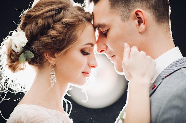 Prachtige bruid en knappe bruidegom elkaar raken door gezichten Premium Foto