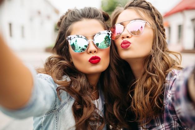 Prachtige brunette vriendinnen met kapsel, gespiegelde zonnebril en rode lippen maken selfie met eendgezicht. Premium Foto