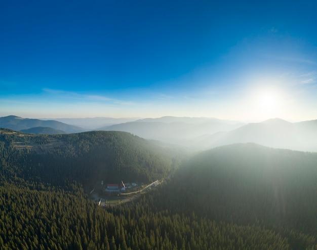 Prachtige dageraad in de bergen, de zonnestralen verlichten de bergtoppen door de mist. Premium Foto