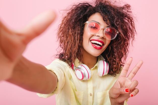 Prachtige gekrulde vrouw met bronzen huid poseren met vredesteken. tevreden zwart meisje in geel overhemd en grote witte oortelefoons. Gratis Foto