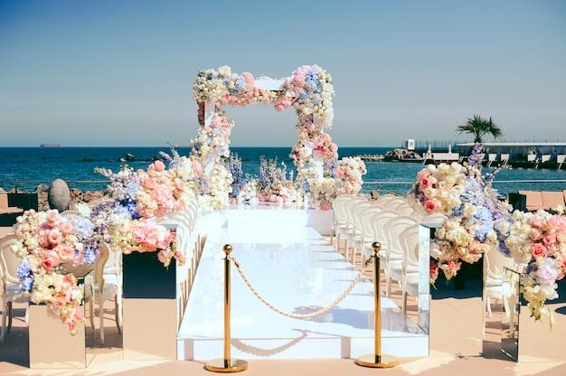 Prachtige huwelijksceremonie plaats in de buurt van de zee versierd met bloemen Gratis Foto
