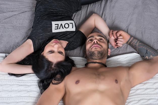 Prachtige internationale paar man met blote borst en brunette vrouw liggend op het grijze gezellige bed in de slaapkamer Premium Foto