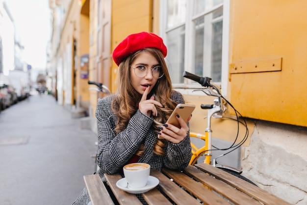 Prachtige jonge blanke vrouw in elegante kledij zittend met telefoon in straatcafé Gratis Foto