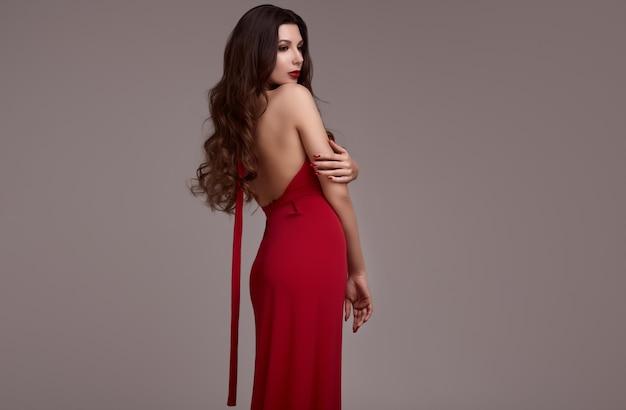 Prachtige jonge brunette vrouw met krullend haar in rode jurk Premium Foto