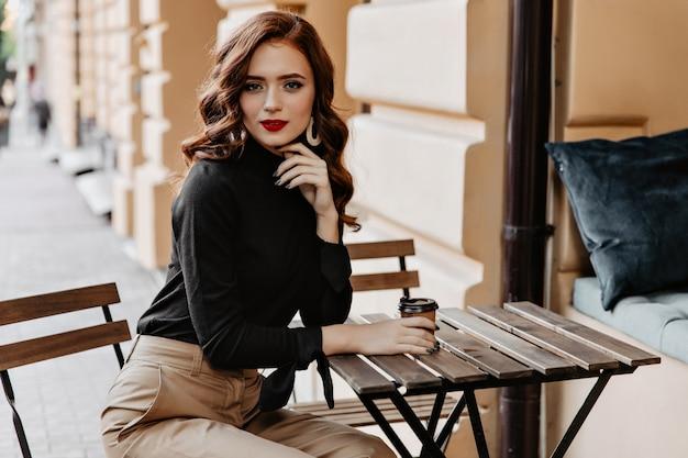 Prachtige jonge dame zittend aan de houten tafel op straat. bevallig gembermeisje dat van koffie geniet openlucht. Gratis Foto