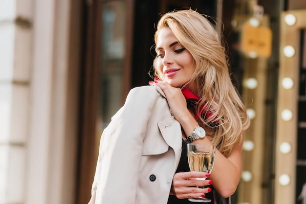 Prachtige jonge vrouw met elegant kapsel wegkijken en glimlachend staande. outdoor portret van geïnspireerde blonde dame met rode manicure met wijnglas. Gratis Foto