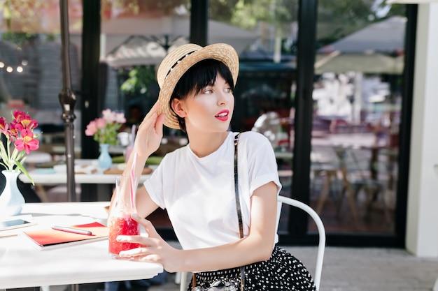 Prachtige jonge vrouw met trendy kapsel koelen in openluchtrestaurant en wegkijken terwijl drankje cocktail Gratis Foto