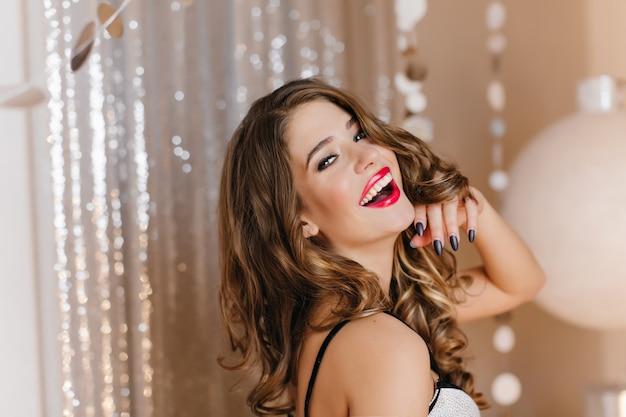 Prachtige jonge witte dame met glanzend donker haar poseren met plezier op kerstfeest. lieve blanke vrouw uiting van geluk tijdens fotoshoot op evenement. Gratis Foto