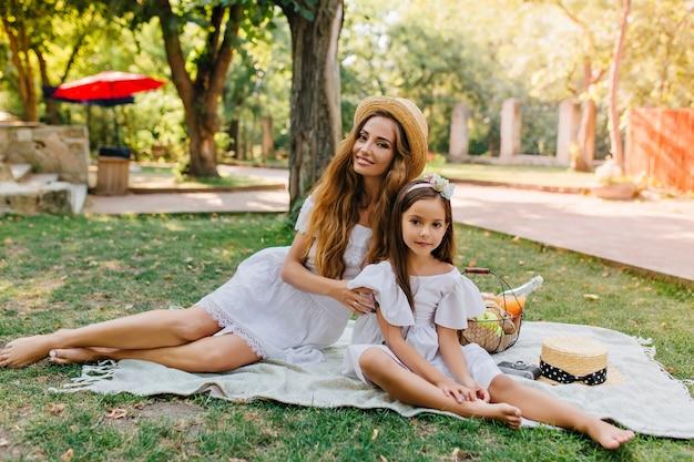 Prachtige langharige vrouw in strooien hoed en witte jurk picknicken met dochter in goede zomerdag. outdoor portret van vrij klein meisje tijd doorbrengen met moeder in park. Gratis Foto
