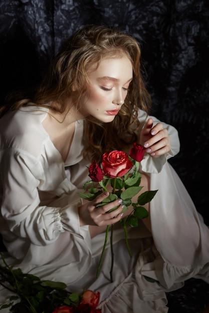 Prachtige lente meisje zit op de vloer met roze bloemen in haar handen. vrouw in een witte jurk droomt, een romantisch beeld. blonde met krullend haar Premium Foto