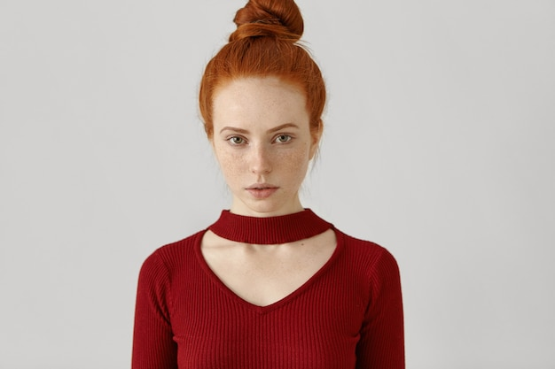 Prachtige luxe blanke roodharige vrouw met haarbroodje en sproeten, gekleed in stijlvolle rode jurk Gratis Foto