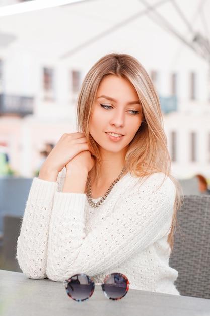 Prachtige mooie jonge vrouw in een gebreide vintage gebreide trui met blauwe ogen zit en droomt in een zomerterras op een zonnige dag. charmante meid geniet van de rest. Premium Foto