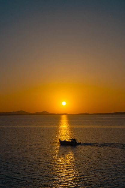 Prachtige oceaan met een kleine boot drijvend op het water bij zonsondergang Gratis Foto