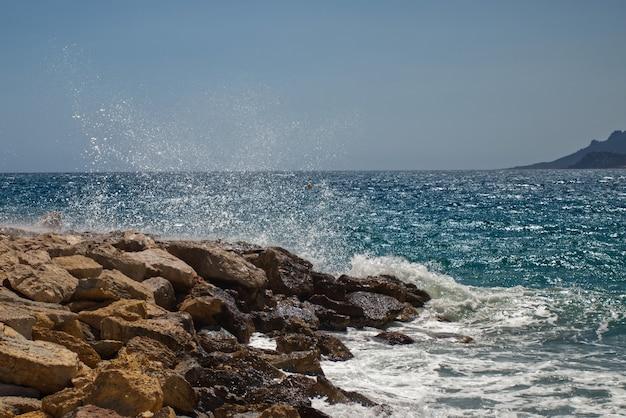 Prachtige oceaangolven komen naar de rotsachtige kusten die in cannes zijn vastgelegd Gratis Foto
