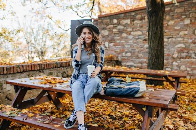 Prachtige slanke dame draagt korte jeans zittend op tafel met gekruiste benen in herfstdag Gratis Foto