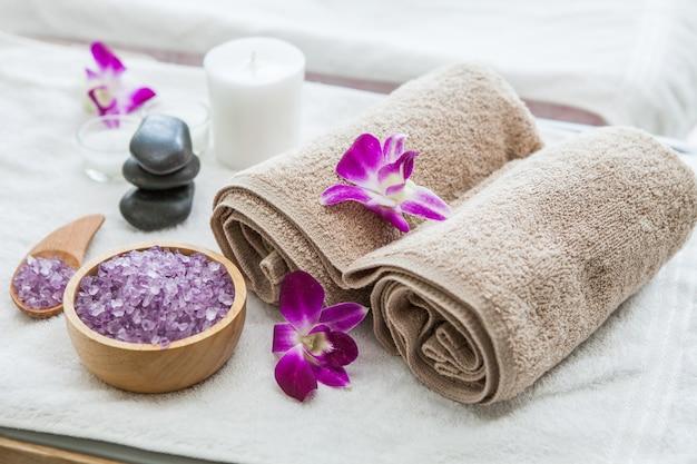Prachtige spa samenstelling behandeling instelling orchidee, handdoeken, badzout, kaars, steen Premium Foto