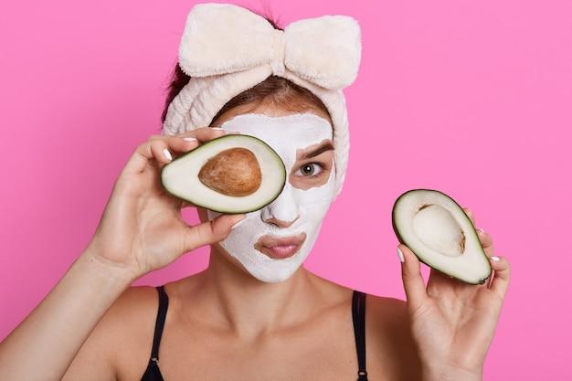 Prachtige spa vrouw met gezichtsmasker op gezicht en helften van avocado in handen houden, camera kijken, cosmetologie procedures thuis doen, haarband met strik dragen. Gratis Foto
