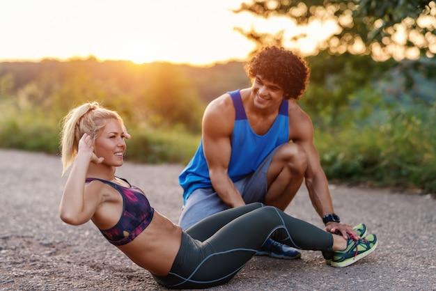 Prachtige sportieve blonde vrouw met paardenstaart crunches terwijl haar vriendje haar benen vasthoudt en haar helpt. landelijke scène, zonnige zomerdag. Premium Foto