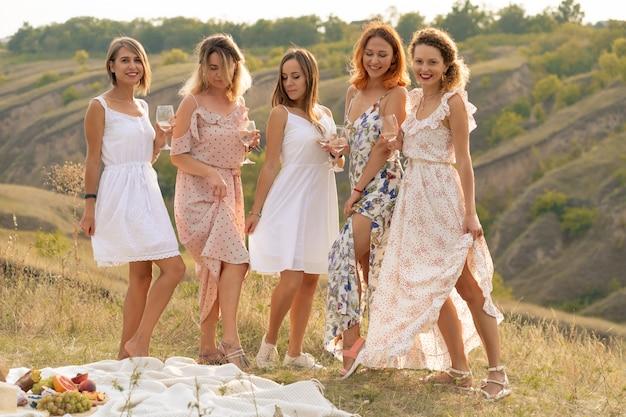 Prachtige vriendinnen plezier hebben en geniet van een zomer groene hlls picknick, dansen en alcohol drinken. mensen concept. Premium Foto