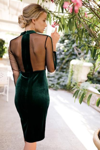 Prachtige vrouw in de groene cocktailjurk die bij de palmboom staat, dun, mode, kapsel, glamoureus, schoenen, buiten, perfect lichaam, blond, schoonheid, bedenken, rug Gratis Foto