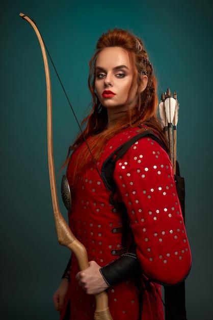 Prachtige vrouw in middeleeuwse tuniek met pijl en boog. Gratis Foto