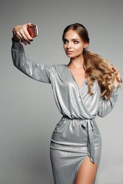 Prachtige vrouw in zilveren avondje uit jurk met lang golvend haar tak Premium Foto