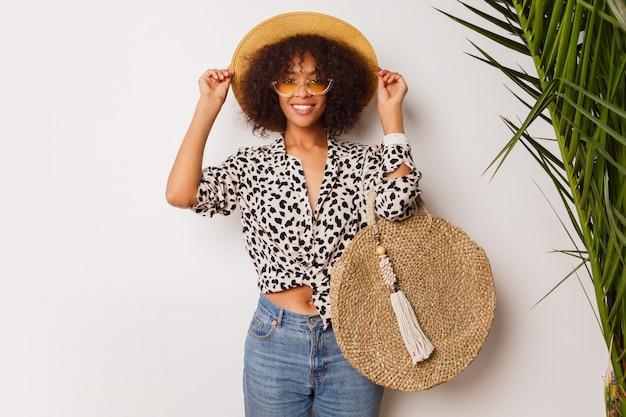 Prachtige vrouw met donkere huid in jeans en strooien hoed poseren in studio op witte achtergrond met tas in bali stijl. soppende stemming. Gratis Foto