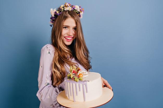 Prachtige vrouw met lang haar poseren met heerlijke taart Gratis Foto