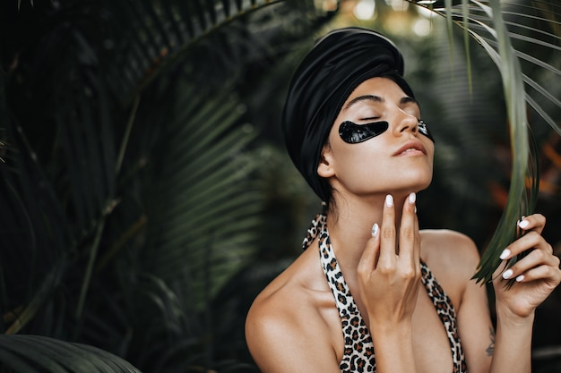 Prachtige vrouw met ooglapjes die kin aanraken. europese vrouw in zwarte tulband poseren op exotische achtergrond. Gratis Foto