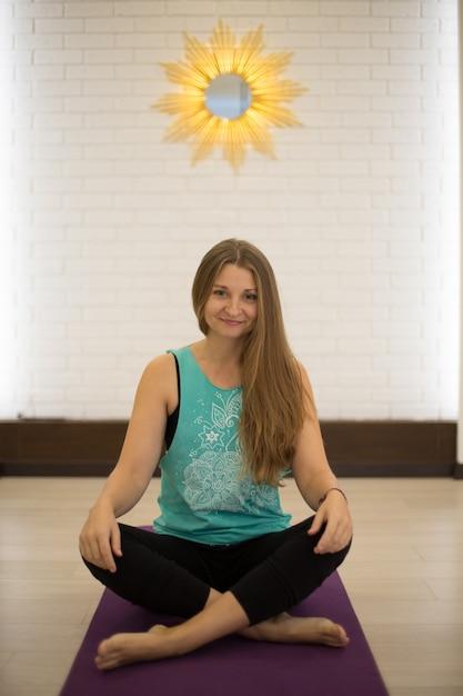 Prachtige vrouw yoga trainer poseren in yogalessen Premium Foto